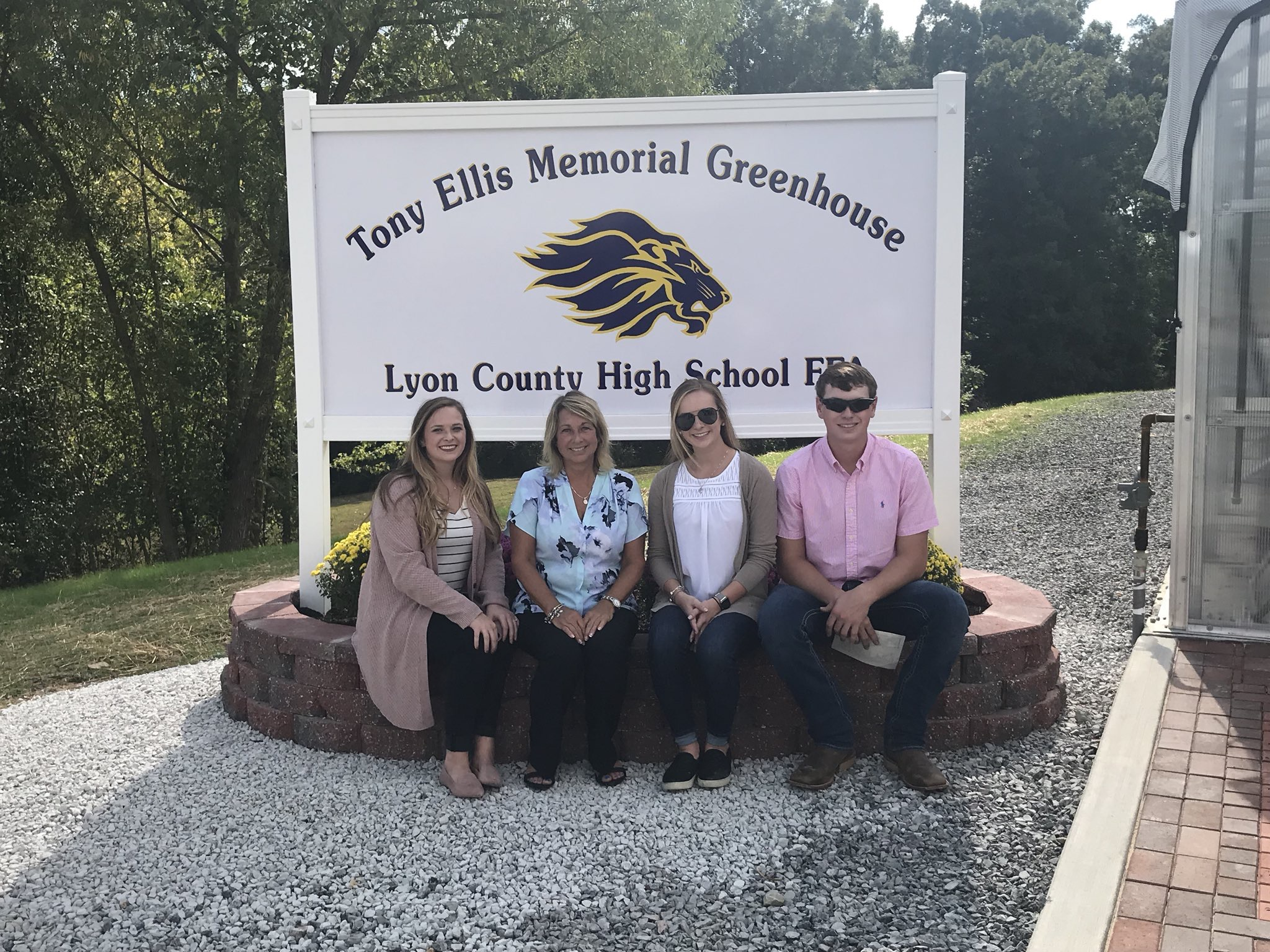 Anna Ellis, Debbie Ellis, Allison Ellis, and Avery Ellis sit in front of the Tony Ellis Memorial Greenhouse sign